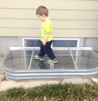 a child walking on a sloped safety top well cover