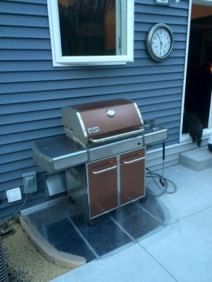 sloped basement well cover on a patio with a grill on top